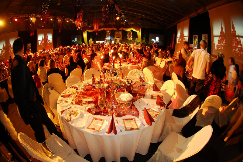 Luxurious Party. A round empty table in a grand New Years party with luxurious banquet and entertainment show