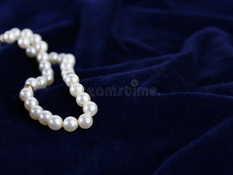 Luxurious Pearl beads on blue velvet. Luxurious set of Pearl beads on blue velvet fabric rich studio setup royalty free stock photos
