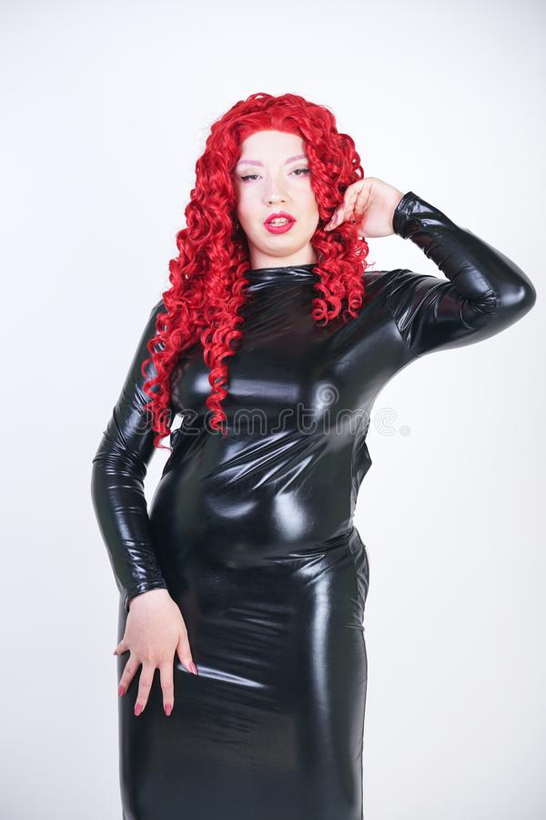 Luxurious plus size woman with Asian face, bright makeup and red curly hair posing in shiny closed long black dress on white backg stock photo