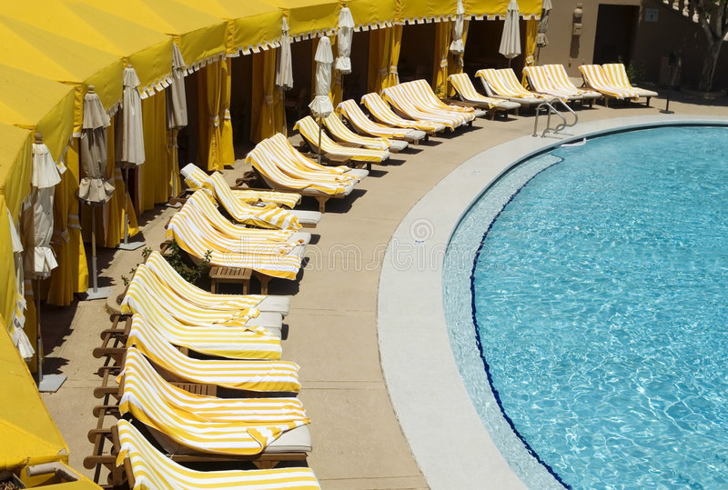 Luxurious poolside cabanas. Luxurious yellow poolside cabanas at high end resort stock photo