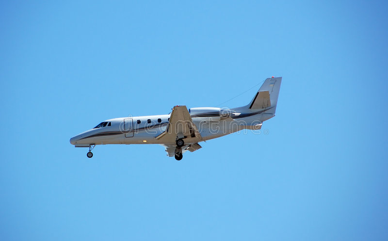 Luxurious private jet approaching airport stock photography