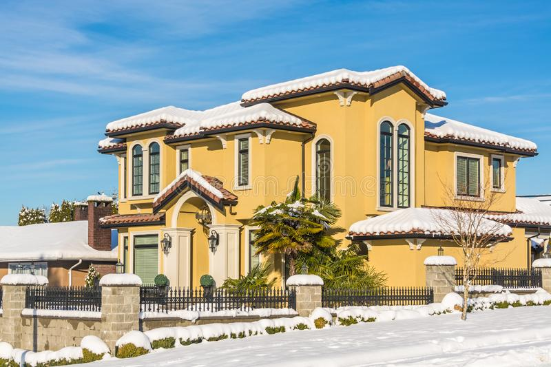 Luxurious residential house in snow on winter sunny day in Canada. Luxurious residential house with front yard in snow. North American family house on winter royalty free stock image