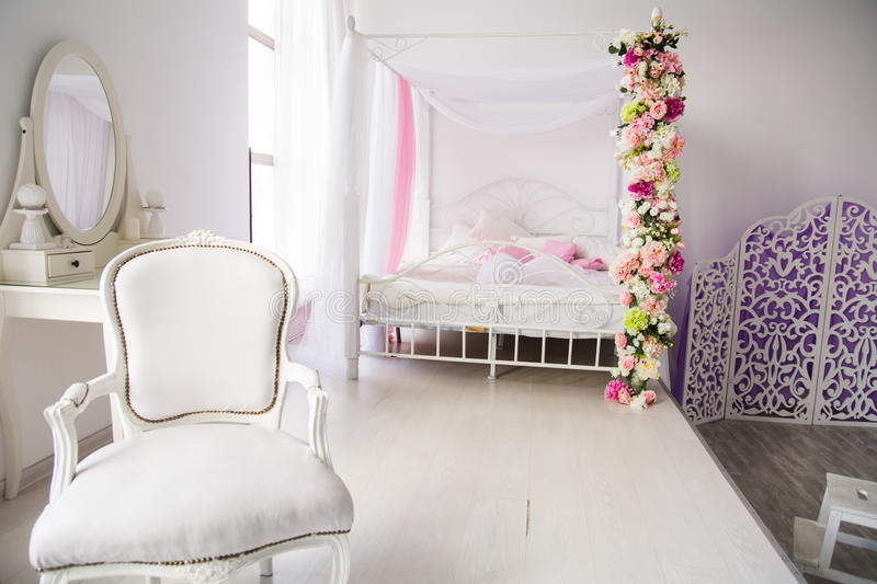 Luxurious room, bedroom with a bed chair and a ladies` table. Interior in a light style with a screen and a mirror royalty free stock photos