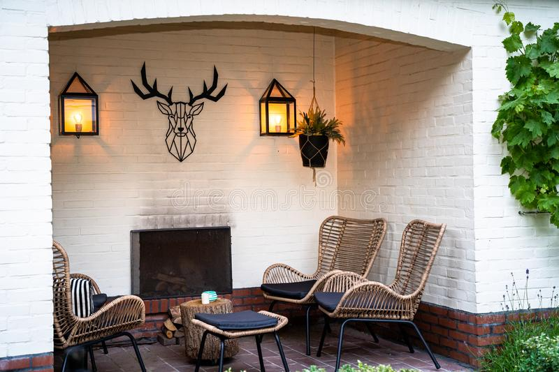Luxurious seating area with fireplace in the garden. Outdoor lounge set in a green garden in the alcove of a white painted building royalty free stock images
