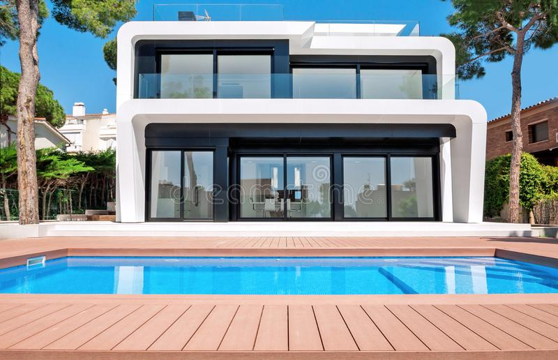Luxurious villa with swimming pool at dusk. External view of a c. Ontemporary house. New technologies in construction royalty free stock photo