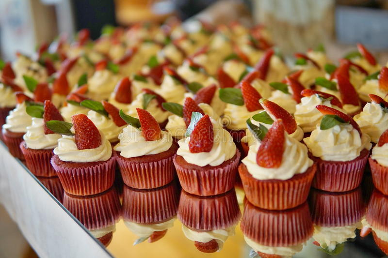 Luxurious wedding cupcakes in red and white color and with strawberry at the top royalty free stock photo