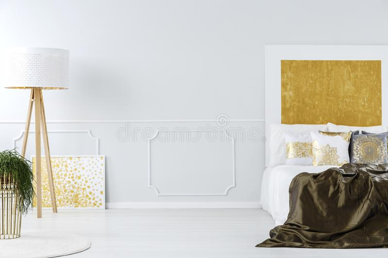 Luxurious white and golden bedroom. Luxurious white and golden minimalist bedroom interior with elegant furniture and a wooden tripod floor lamp royalty free stock image