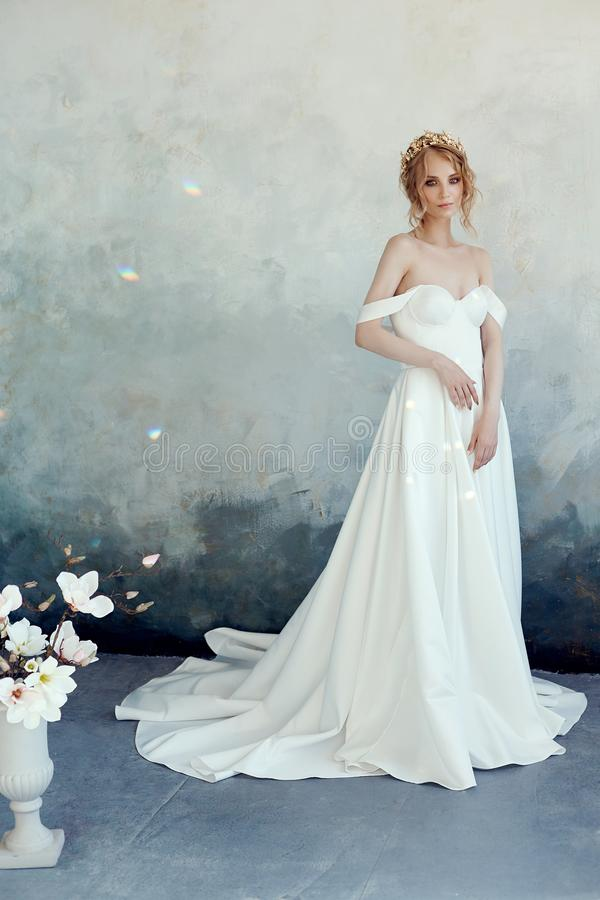 Luxurious white wedding dress on the girl`s body. New collection of wedding dresses. Morning bride, a woman waiting for the groom. Before the wedding ceremony stock photography