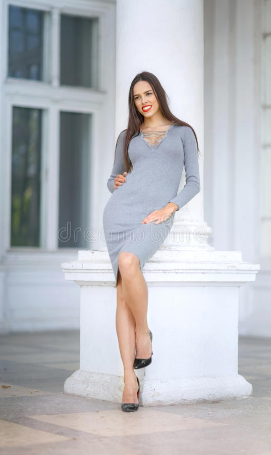 A luxurious woman in light gray dress near a white column. The confident girl is posing outdoors. The amazing lady in stock images