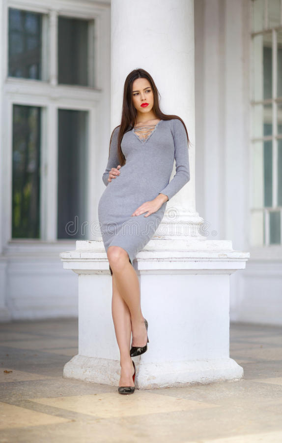 A luxurious woman in a light gray dress before a white column. The pretty girl is posing outdoors. The lady in dress and royalty free stock photos