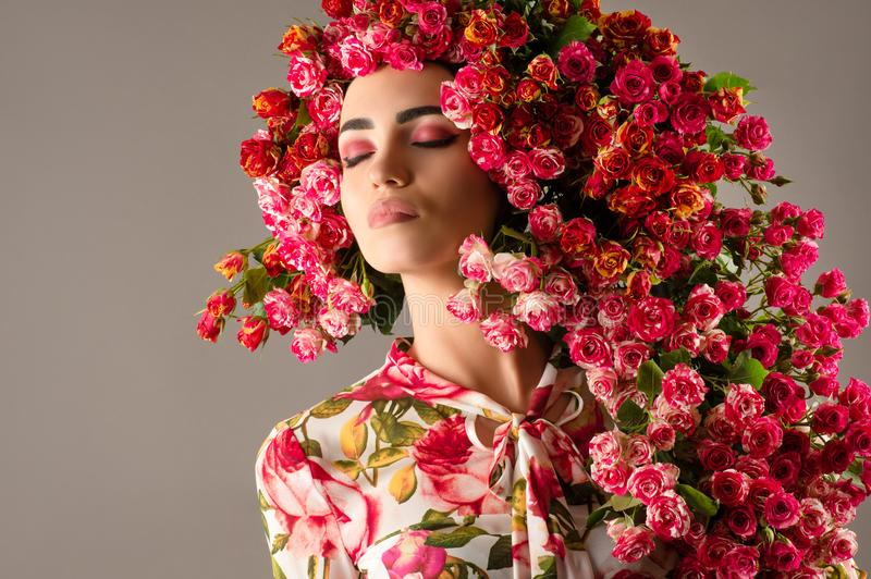 Luxurious woman with red roses flower, fashionable hairstyle royalty free stock photography