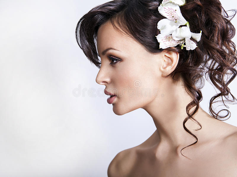 Luxurious young woman brunette with long curly hairs - over white background royalty free stock photo