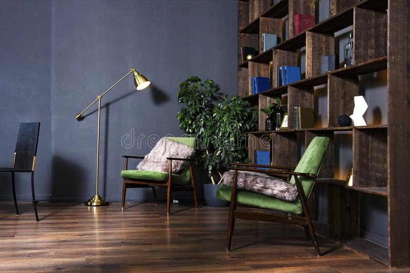 Luxury apartment interior with bookshelves, sconces lamp and a comfortable chair. royalty free stock images