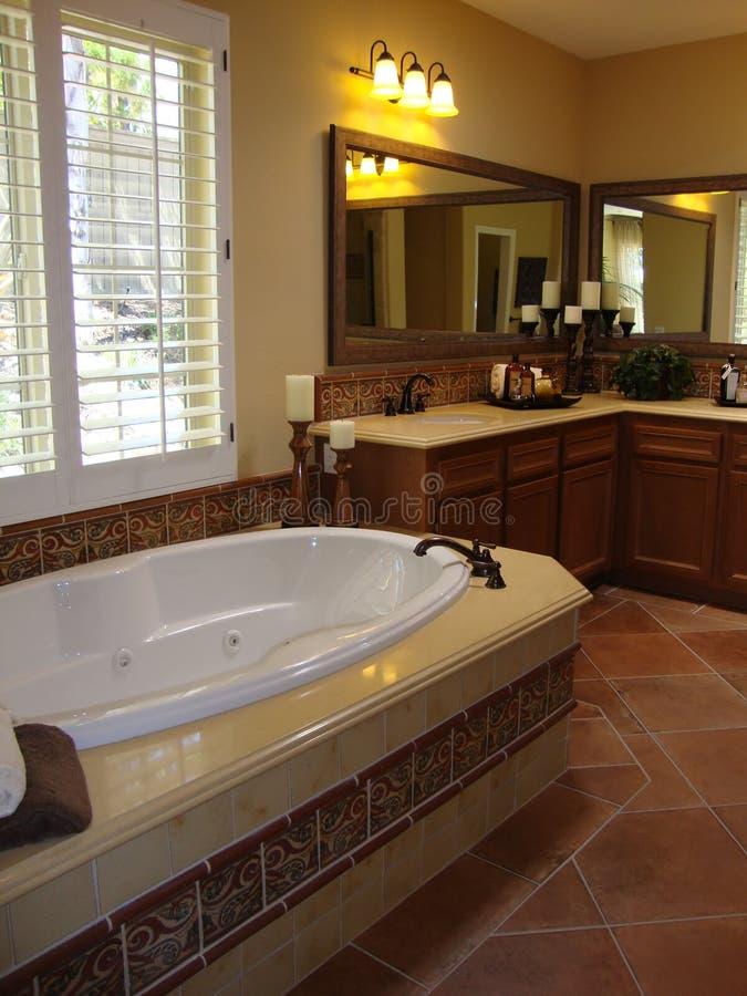 Luxury Bathroom. Beautiful luxury bathroom with dark wood cabinets and tile floors, white wood shudders stock photography