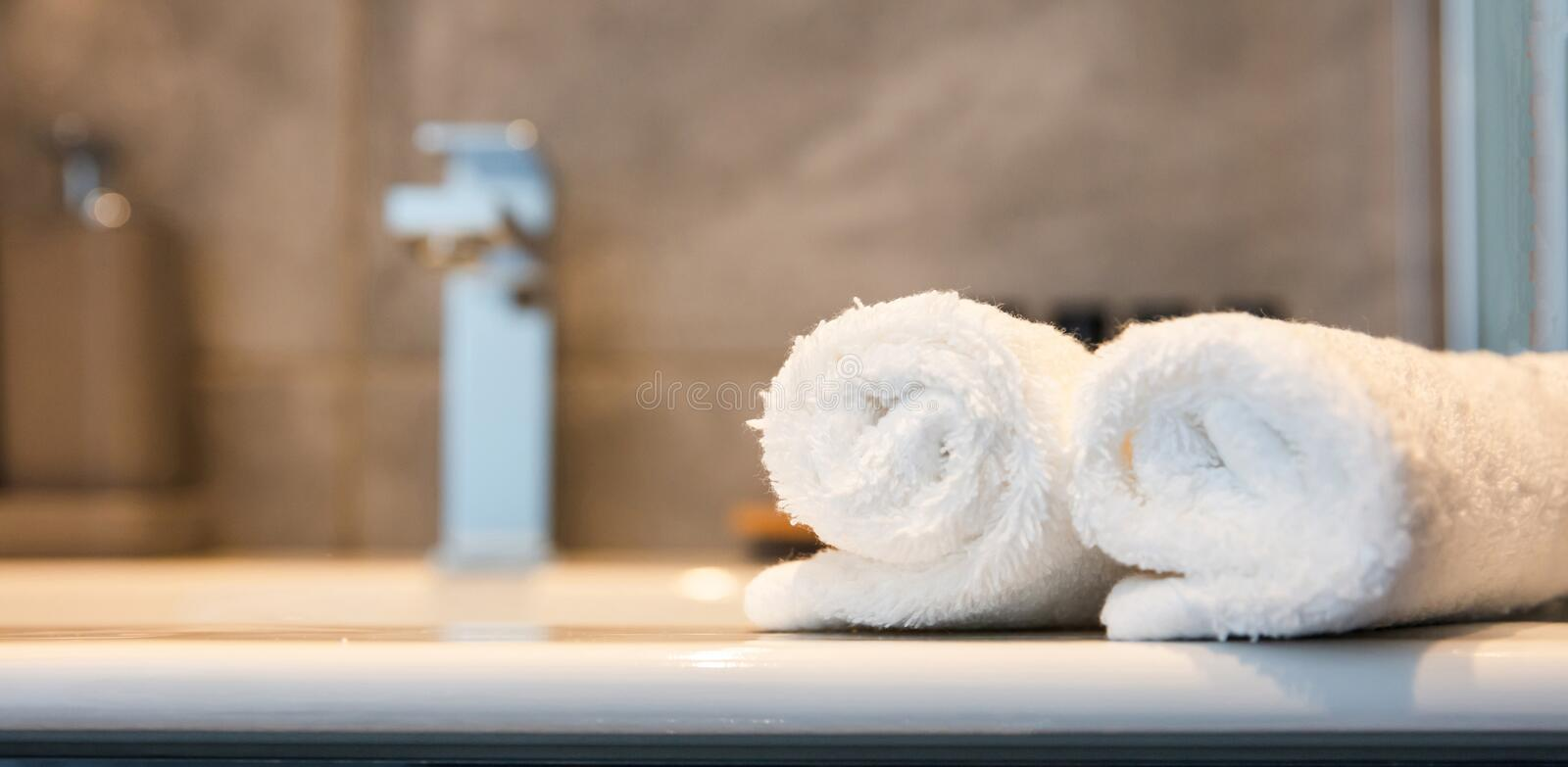 Luxury bathroom sink and white towels. Closeup view with details. Bathroom interior. Blur sink and white roll ups of hand towels. Closeup view with details royalty free stock image