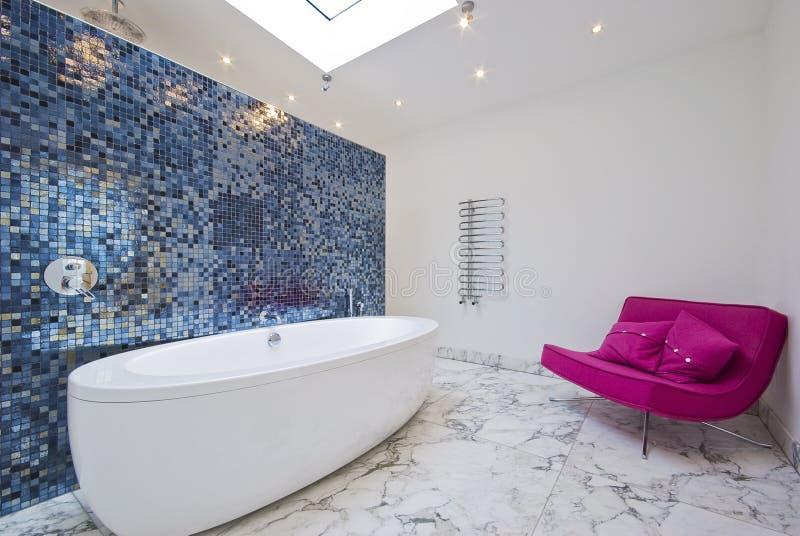 Luxury bathroom with sofa. Modern luxury bathroom with pink sofa mosaic tiles and marble floor stock photo