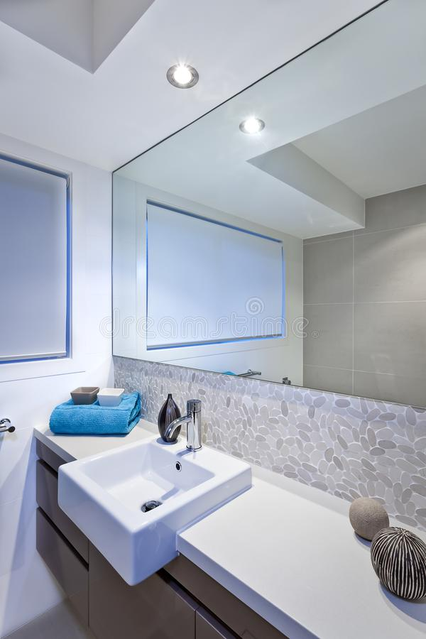 Luxury bathroom with wide mirrors and tap and sink. Attached to white countertop in a luxury hotel or house stock images
