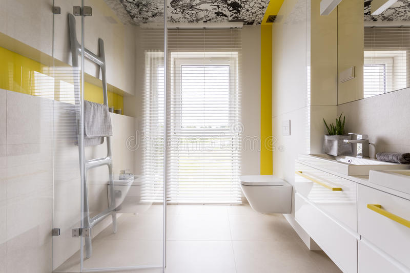 Luxury bathroom with yellow details. Luxury stylish bathroom with white cabinets, mirror, ladder tower rack, window, glass door and yellow details royalty free stock photography