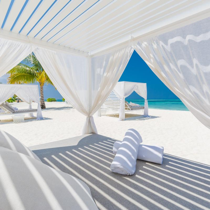 Luxury beach background. White beach tent and loungers and blue sea background and palm trees and blue sky stock photography
