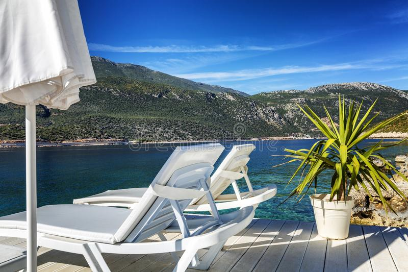 Luxury beach in a beautiful bay with white deck chairs. Magnificent views of the sea and mountains on a sunny day. Horizontal stock photos