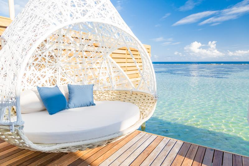 Luxury beach resort, beautiful cozy white lounger near pool, perfect place for honeymoon, gorgeous seascape in overcast weather stock photos