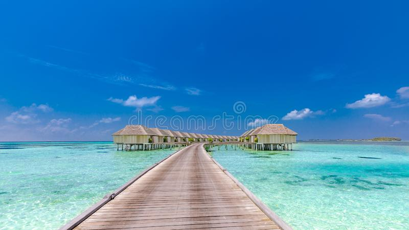 Maldives island, luxury water villas resort and wooden pier. Beautiful sky and clouds and beach background for summer vacation. Luxury beach resort, over water stock photos