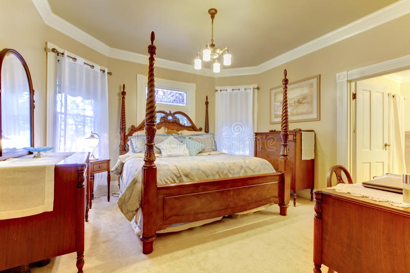 Luxury bedroom with high pole carved wood bed, nightstand and va. Luxury beige and brown bedroom with high pole carved wood bed, nightstand and vanity cabinet stock image