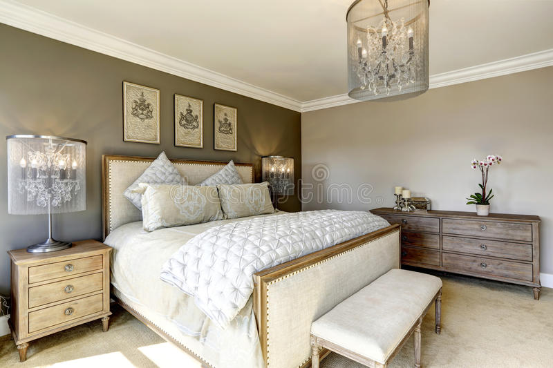Luxury bedroom interor. Luxury bedroom interior with carved wood bed, dresser and nightstands royalty free stock photos