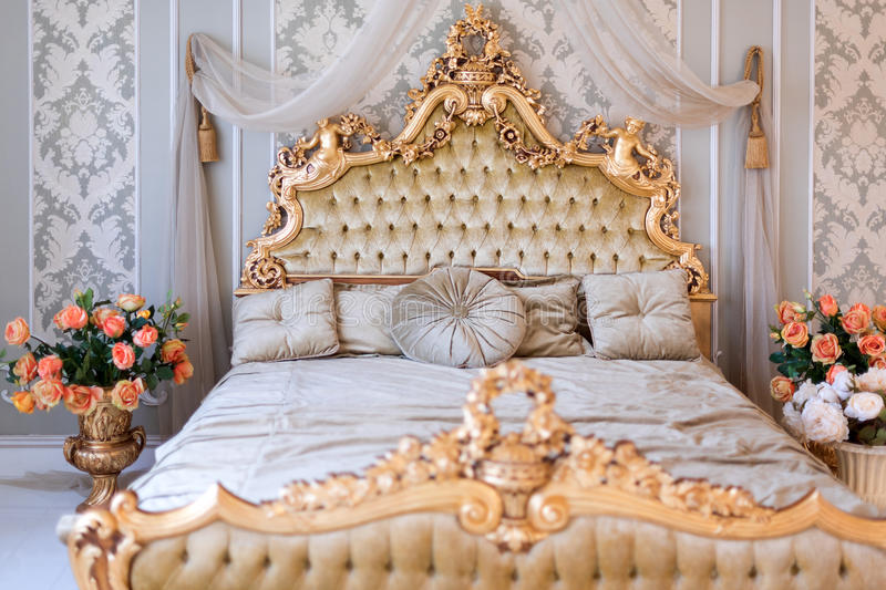 Luxury bedroom in light colors with golden furniture details. Big comfortable double royal bed in elegant classic. Interior stock image