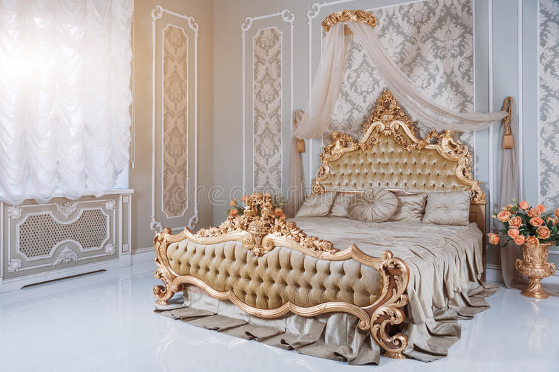 Luxury bedroom in light colors with golden furniture details. Big comfortable double royal bed in elegant classic. Interior stock photos