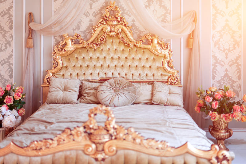 Luxury bedroom in light colors with golden furniture details. Big comfortable double royal bed in elegant classic. Interior. Toned picture royalty free stock photography