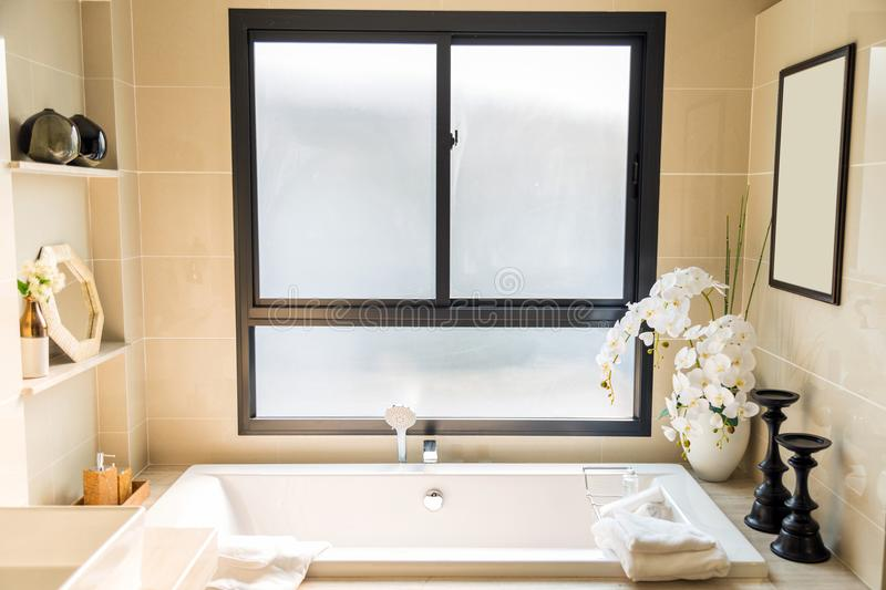 A luxury biege bathroom with a white bathtub and white towel wit stock photo