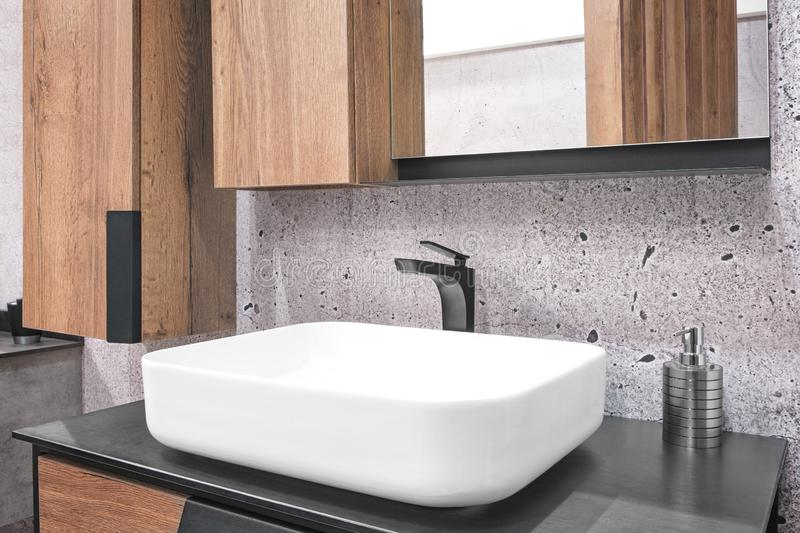 Luxury black faucet mixer on a white sink in a beautiful violet gray bathroom.  stock image