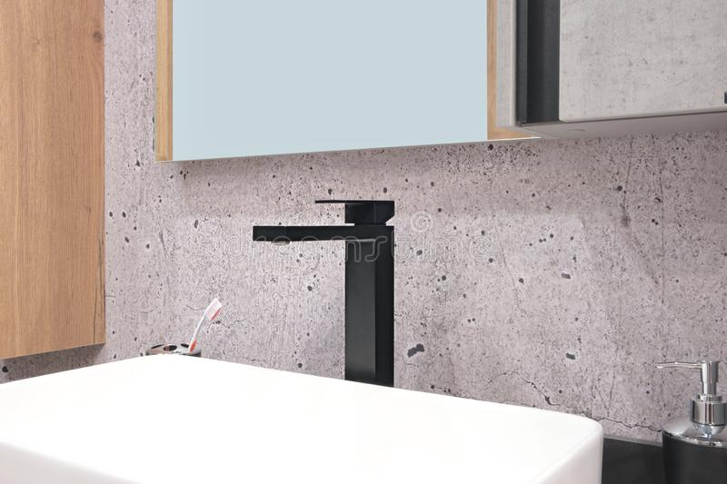 Luxury black faucet mixer on a white sink in a beautiful violet gray bathroom.  royalty free stock photos