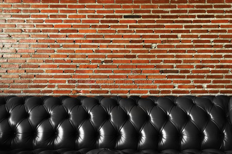 Luxury black leather retro sofa with red brown brick wall interior design background stock images