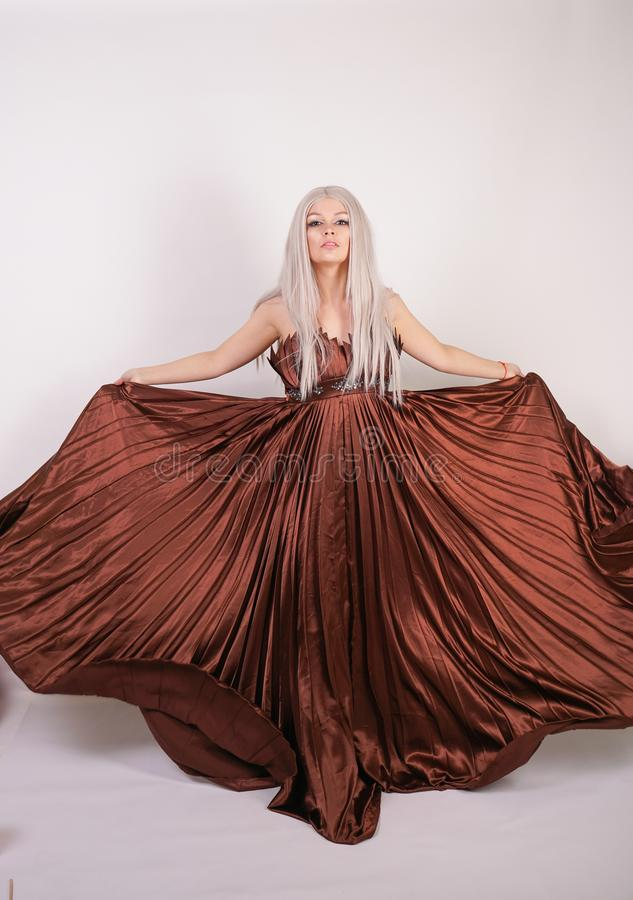Luxury blonde caucasian model girl in chocolate color long evening dress made of pleated fabric waving a flying dress and stands o royalty free stock images