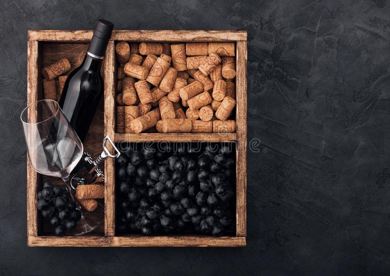 Luxury bottle of red wine and empty glass with dark grapes with corks and corkscrew inside vintage wooden box on black stone stock photos