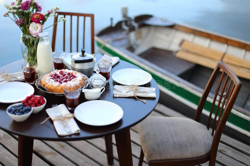 Luxury breakfast on the river. Table served with delicious homemade pie, berries, tea and coffe on nature background royalty free stock photos