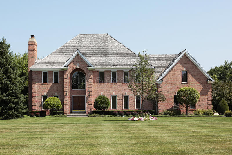 Luxury brick home with arched entry. Luxury brick home in suburbs with arched entry royalty free stock photography