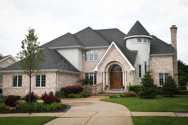 Luxury Brick House. Image of a single family home with many windows and beautiful landscaping stock photos