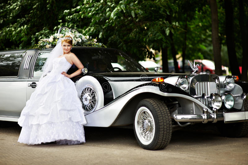 Luxury bride in wedding dress about limousine. Luxury bride in white wedding dress about big retro limousine stock photo