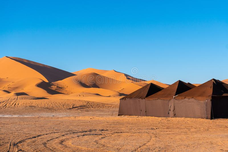 Luxury brown tent camp in Sahara Desert Merzouga, Morocco on a sunny day with sand dunes on background stock photography
