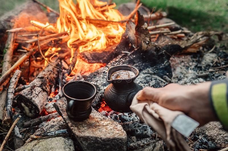 Luxury camping concept. Fresh coffee prepared in turkish cezva o. N campfire coals royalty free stock photography