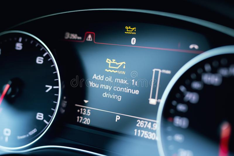 Luxury car color screen dashboard with warning message. Low engine oil level indication. Intelligent Driver Information System royalty free stock photography
