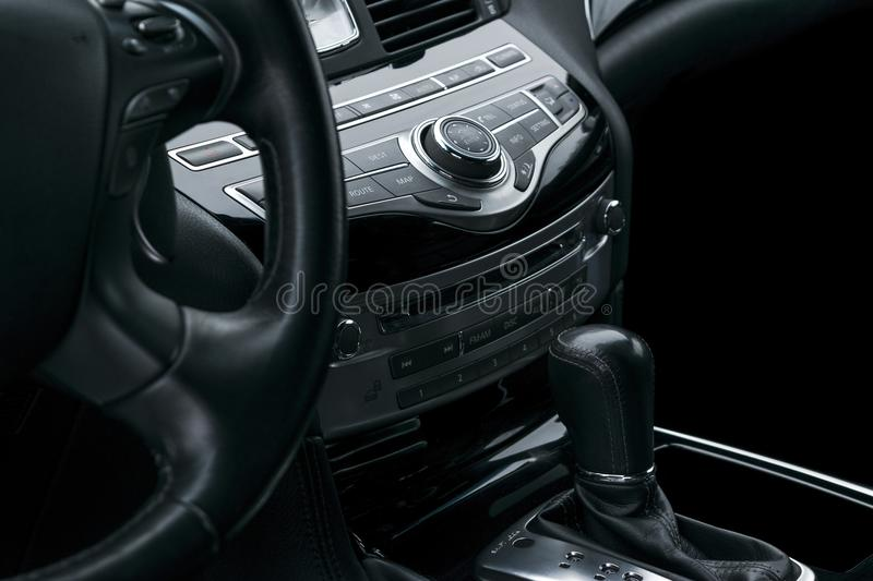 Luxury car inside. Interior of prestige modern car. Automatic gear shift. Black perforated leather cockpit. Media control buttons stock photo