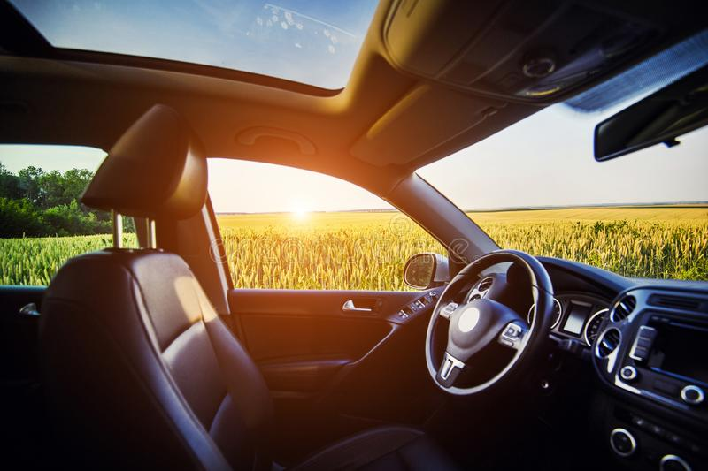 Luxury car inside interior. Steering wheel, shift lever, leather salon, dashboard and panoramic roof. crossover SUV in the. Countryside with sunset in the royalty free stock photos