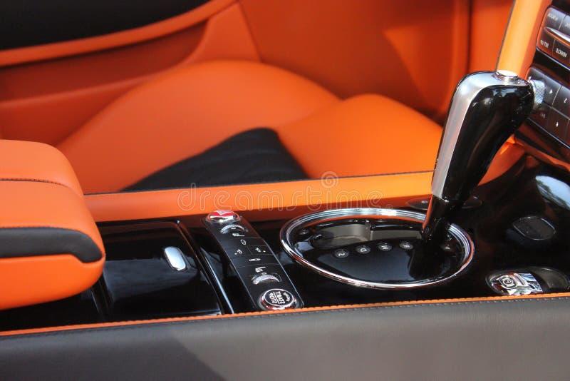 Luxury car Interior - steering wheel, shift lever and dashboard. Orange stock photo