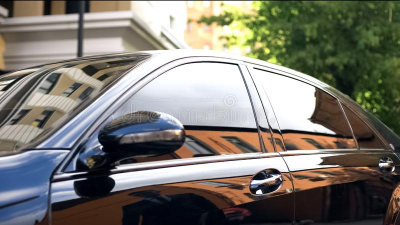 Luxury car with tinted glass standing at parking, reflection of businessman stock images