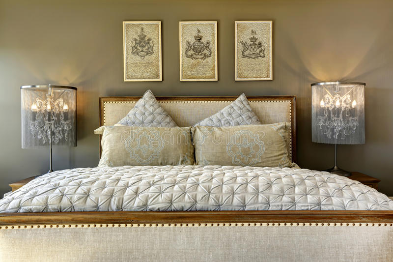Luxury carved wood bed with pillows. Luxury bedroom furniture. Carved wood bed with pillows and lamps on nightstands stock image