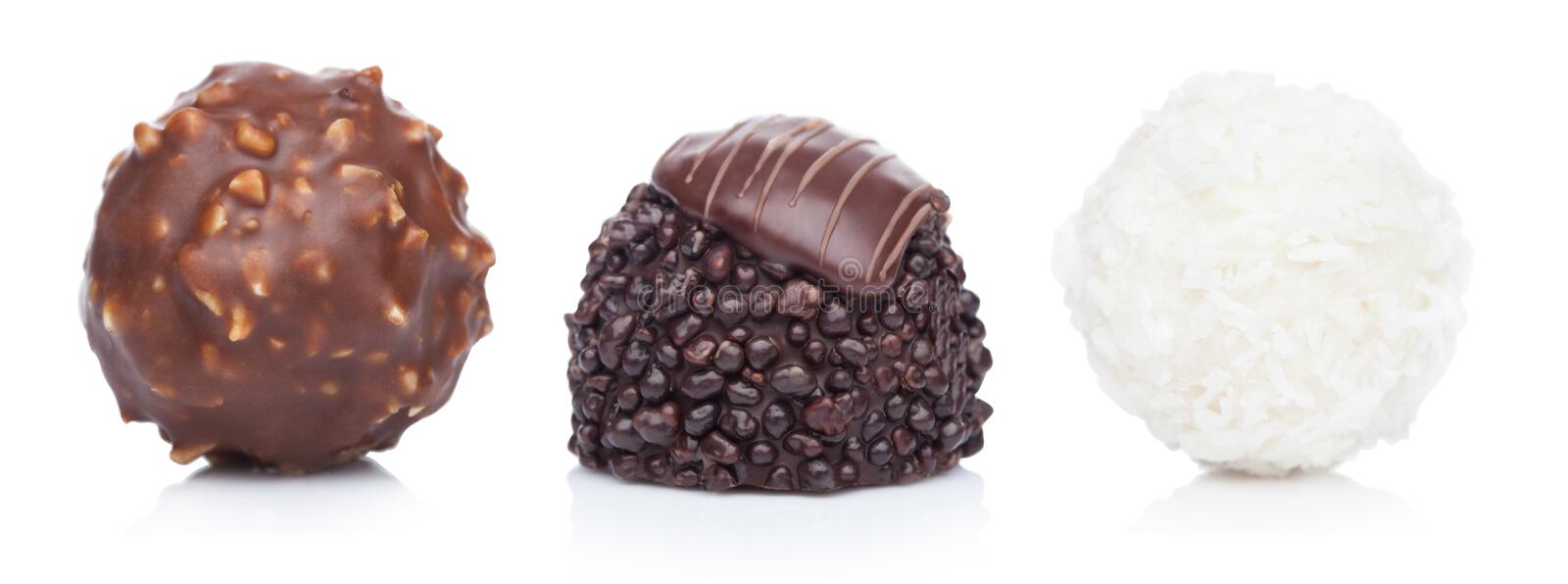 Luxury chocolate candies with hazelnuts and white cream with coconut flake round candies and dark chocolate candy on white royalty free stock photo
